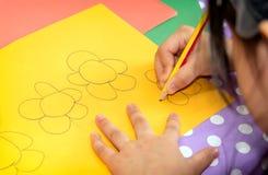 Kind zeichnet Blumen auf einem Stück farbigem Papier stockfotos
