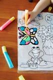 Kind zeichnet ein beflecktes Schwarzes Stockfotos