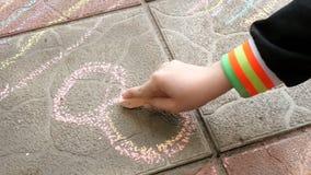 Kind zeichnet ein Stück Kreide auf dem Pflasterstein stock video