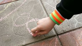 Kind zeichnet ein St?ck Kreide auf dem Pflasterstein stock video footage