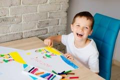 Kind zeichnet eine Zeichnung der glücklichen Familie auf dem Strand Lizenzfreie Stockfotografie