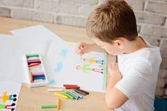 Kind zeichnet eine Zeichnung des glücklichen Sohns und des Vaters Lizenzfreies Stockfoto