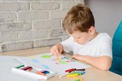 Kind zeichnet eine Zeichnung des glücklichen Sohns und des Vaters Lizenzfreie Stockfotos