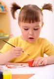 Kind zeichnet mit Lacken im Vortraining lizenzfreie stockfotografie