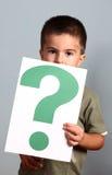 Kind zeigt Fragezeichen Stockfoto