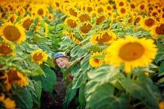 Kind in zonnebloemen stock fotografie