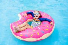 Kind in zwembad op doughnutvlotter stock fotografie
