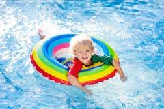 Kind in zwembad op stuk speelgoed ring De jonge geitjes zwemmen royalty-vrije stock afbeeldingen
