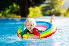 Kind in zwembad op stuk speelgoed ring De jonge geitjes zwemmen stock afbeelding
