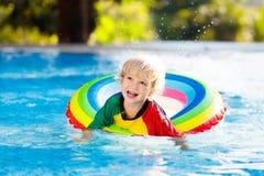 Kind in zwembad op stuk speelgoed ring De jonge geitjes zwemmen royalty-vrije stock fotografie