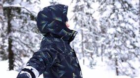 Kinddalingen in de sneeuw in langzame motie Actieve sporten in openlucht De winter zonnige dag stock videobeelden