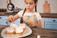 Kinddochter in de keuken die cakes verfraaien wordt zij gemaakt met haar mamma weinig helper, eigengemaakt voedsel royalty-vrije stock afbeelding
