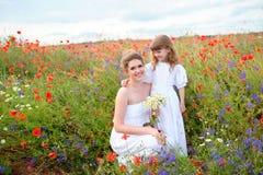Kinddochter die haar mooie moeder onder de rode bloem koesteren Royalty-vrije Stock Afbeeldingen