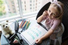 Kinddochter het schilderen prentbriefkaar voor mamma Meisjeszitting thuis op lijst, daarna het liggen roze bloem voor moeder Het  royalty-vrije stock fotografie