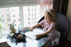 Kinddochter het schilderen prentbriefkaar voor mamma Meisjeszitting thuis op lijst, daarna het liggen roze bloem voor moeder Het  royalty-vrije stock foto's