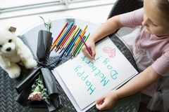 Kinddochter het schilderen prentbriefkaar voor mamma Meisjeszitting thuis op lijst, daarna het liggen roze bloem voor moeder Het  royalty-vrije stock afbeeldingen