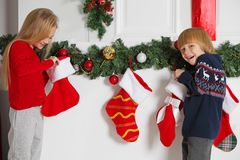 Kinder öffnet Weihnachtsstrumpf stockfotos