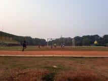 Kinder üben Fußball während des Nachmittages und laufen stockfoto