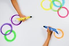 Kinder übergibt das Halten Stiften von des von Drucken 3d mit Fäden auf weißem Hintergrund Beschneidungspfad eingeschlossen Stockfotos