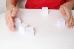 Kinder übergibt Spiel mit fünf kleinen Papierwürfeln Lizenzfreie Stockbilder