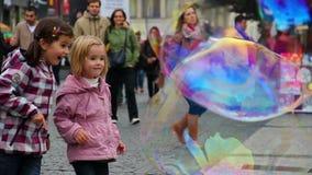 Kinder überrascht durch enorme Seifenblasen auf der Straße stock footage
