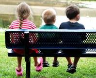 Kinder auf Bank Stockbild