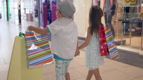 Kinder auf dem Einkaufen, stilvolle Kinderfreunde mit Käufen in die Hände, die herein durch Shopfenster am Mall nach Kauf gehen stock video footage