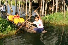 Kinder auf dem Rudern eines Bootes am Dorf von Maing Thauk lizenzfreie stockfotos