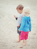 Kinder auf dem Strand, der Sammelnmuscheln spielt stockbild