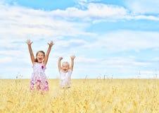 Kinder auf dem Weizengebiet Stockfotos