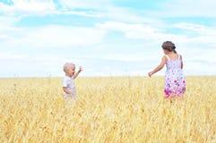 Kinder auf dem Weizengebiet stockbild