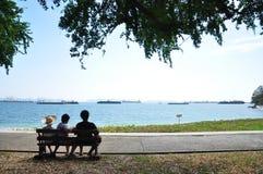 Kinder auf der Bank betrachten das Meer Stockbild