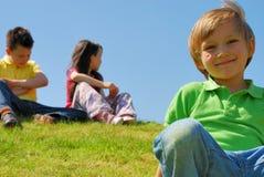 Kinder auf einem grasartigen Hügel Lizenzfreies Stockbild