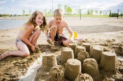 Kinder auf einem Strand mit Sandschloss Stockbild