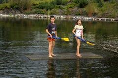 Kinder auf Floßholdingpaddeln Stockbild