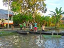 Kinder auf hölzernem Pier durch Fluss Lizenzfreie Stockfotos