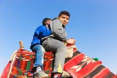 Kinder auf Kamel in Giseh-Pyramiden lizenzfreie stockbilder