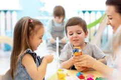 Kinder auf Kunstunterrichten mit Lehrer im Kindergarten stockfotos