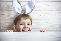 Kinder auf Osterei jagen in blühendem Frühlingsgarten Kinder, die nach bunten Eiern in der Blumenwiese suchen Kleinkindjunge und  Lizenzfreies Stockbild