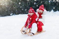 Kinder auf Pferdeschlitten Kinderschlitten Winterschneespaß stockfotografie