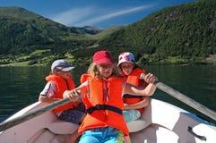 Kinder auf Reihenboot Stockfotografie