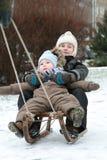 Kinder auf Schlitten Stockfotos