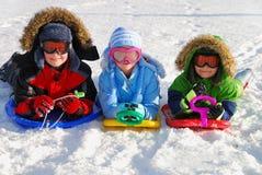 Kinder auf Schlitten im Schnee Stockfotos