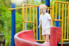 Kinder auf Spielplatz Kinderspiel im Sommerpark stockbilder