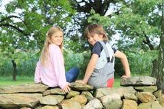 Kinder auf Steinwand Stockfotos
