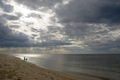 Kinder auf Strand, drastischer Himmel, stürmische Wolken Lizenzfreies Stockfoto