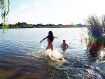 Kinder baden im Fluss lizenzfreie stockbilder