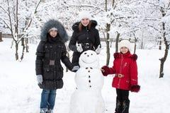 Kinder bauen den Schneemann auf Stockbild