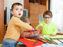 Kinder bei Tisch mit Zeichenstiften Stockfotos