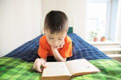 Kinder Bildung, Jungenlesebuch, das auf Bett, Kinderporträt lächelt mit Buch, interessantes Märchenbuch liegt lizenzfreie stockfotografie